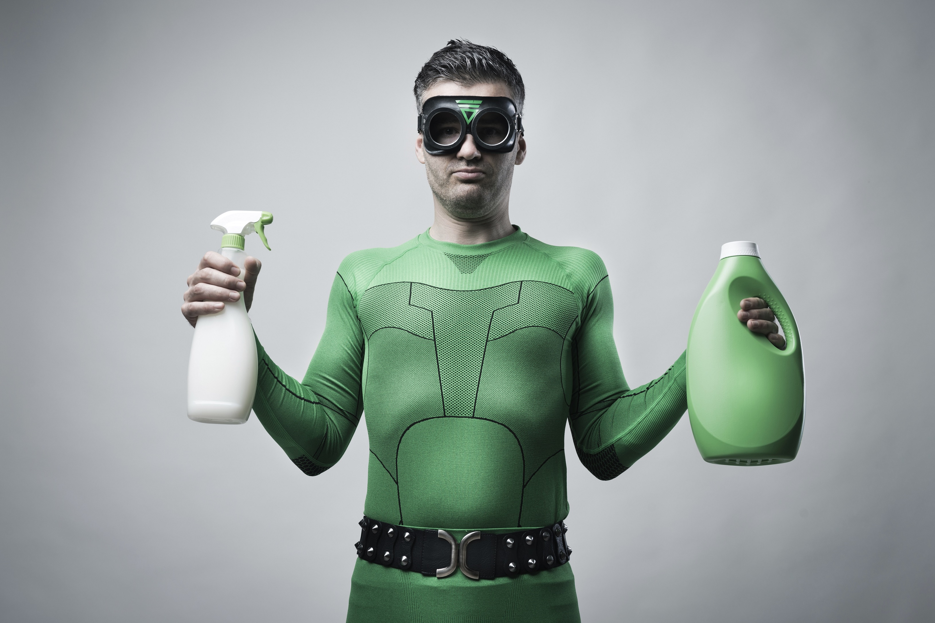 Green superhero showing spray detergent and laundry detergent.